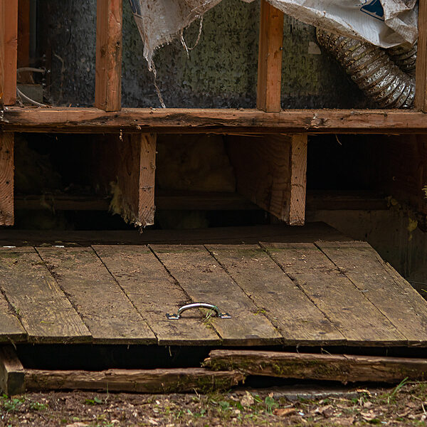 old wooden hatch to crawlspace damaged and splintered