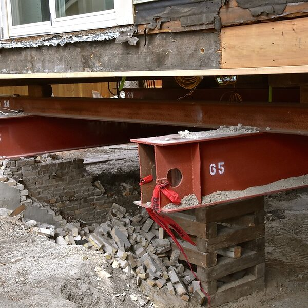old house rests on 65 foot long steel girders as a new concrete basement and foundation is being constructed.